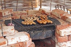 Sausages are cooked on the grill in fireplace. Made from bricks royalty free stock image