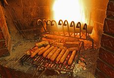 Sausages cooked on the grill of a fireplace. For a village festival royalty free stock image