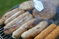 Sausages cooking on barbecue Stock Photos