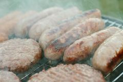 Sausages cooking on barbecue Royalty Free Stock Image