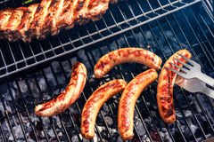 Sausages cooking on barbecue grill for summer outdoor party. Foo. D background with barbecue party Royalty Free Stock Photos