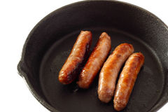Sausages cooking cast iron pan Royalty Free Stock Photo