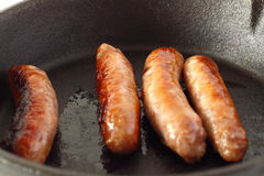 Sausages cooking cast iron pan Royalty Free Stock Image