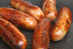Sausages Cooking in Frying Pan. Six pork sausages frying in non-stick skillet Stock Photography