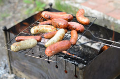 Sausages cooking on a portable barbecue Royalty Free Stock Photo