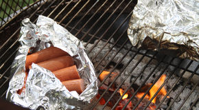 Sausages in foil on a wood fire grill Royalty Free Stock Photo