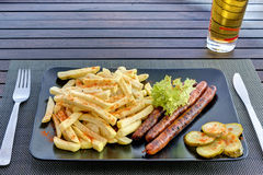 Sausages with french fries on black plate Stock Images