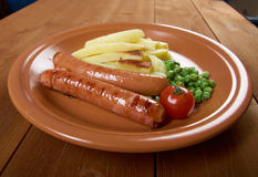 Sausages with french fries Stock Images