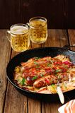 Sausages fried in cast iron skillet with two beer mugs. On wooden background Stock Image