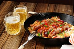 Sausages fried in cast iron skillet with two beer mugs. On wooden background Royalty Free Stock Image