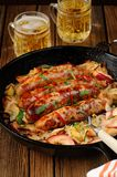 Sausages fried in cast iron skillet with two beer mugs Stock Photo