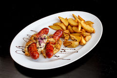 Sausages and fried potatoes. Dellicious wrapped sausages and fried potatoes on a white plate food photography Royalty Free Stock Image