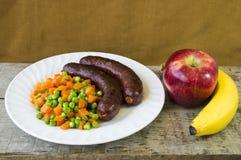 Sausages and fruits Stock Photos