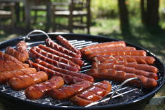 Sausages frying on a grill Royalty Free Stock Photography