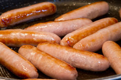 Sausages frying in oil in the pan Royalty Free Stock Image