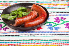 Sausages in frying pan with basil Royalty Free Stock Photography
