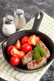 Sausages in a frying pan on black background. Fresh tomate and p Stock Images