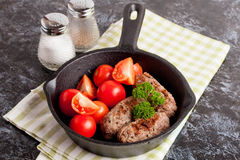 Sausages in a frying pan on black background. Fresh tomate Stock Photos