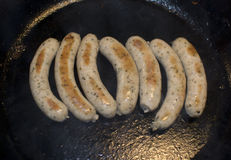 Sausages in frying pan Stock Photos