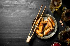 Sausages in a frying pan with a glass of beer. Stock Image
