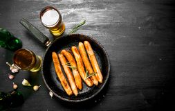 Sausages in a frying pan with a glass of beer. Stock Photo