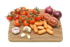 Sausages, garlic and cherry tomatoes on a cutting board isolated Royalty Free Stock Images