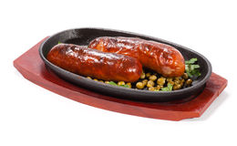 Sausages with green peas. Sausages on serving frying pan royalty free stock images