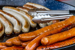 Sausages on a Griddle. A close up image of sausages cooking on a large griddle at a farmers market Stock Photos