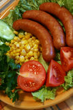Sausages a grill. On leaves of salad about a tomato, cucumbers and corn Royalty Free Stock Photos