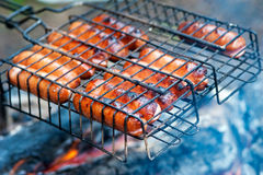 Sausages on a grill. BBQ Hot Dogs on the Grill Stock Photos