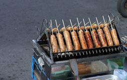 Sausages on a grill. A roadside stand with sausages cooking on a charcoal grill Stock Image