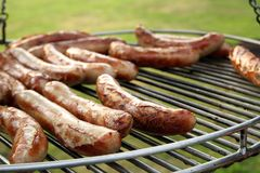 Sausages on grill in garden Stock Photos