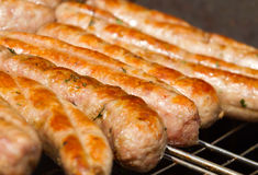 Sausages on a grill. Grilling Sausages on barbecue grill Royalty Free Stock Images