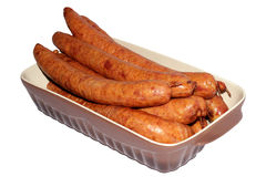 Sausages grill. Sausages for grilling in the cruets on a white background Royalty Free Stock Photo