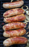 Sausages on grill with onions Royalty Free Stock Images