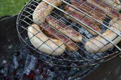 Sausages on grill over fire Royalty Free Stock Photography