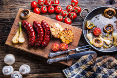 Sausages. Grill sausages. Grilled sausage with mushrooms garlic tomatoes and onions Stock Images