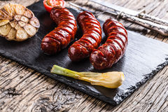 Sausages. Grill sausages. Grilled sausage with mushrooms garlic tomatoes and onions Royalty Free Stock Image