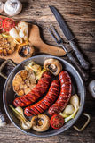 Sausages. Grill sausages. Grilled sausage with mushrooms garlic tomatoes and onions Stock Image