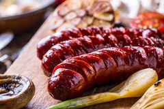 Sausages. Grill sausages. Grilled sausage with mushrooms garlic tomatoes and onions Royalty Free Stock Images