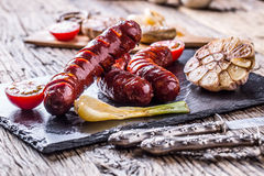 Sausages. Grill sausages. Grilled sausage with mushrooms garlic tomatoes and onions Stock Photography