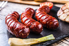 Sausages. Grill sausages. Grilled sausage with mushrooms garlic tomatoes and onions Royalty Free Stock Photography