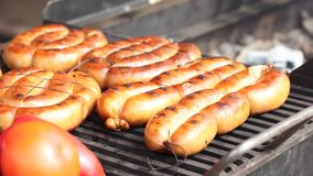Sausages on a grill with tomatoes and sweet peppers stock footage