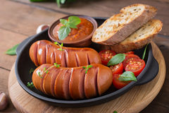 Sausages on the grill with vegetables. Royalty Free Stock Images