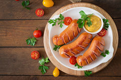 Sausages on the grill with vegetables. Top view Stock Photos