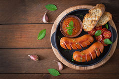 Sausages on the grill with vegetables. Top view Royalty Free Stock Photography