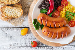 Sausages on the grill with vegetables. Top view Royalty Free Stock Image