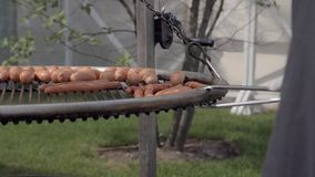 Sausages grilled on a BBQ. Slow motion shot of pork sausages grilled on a portable BBQ.Summer picnic, close up of the grill, meat and fire stock video