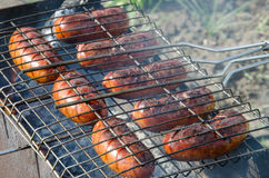 Sausages grilled over charcoal barbecue Royalty Free Stock Images
