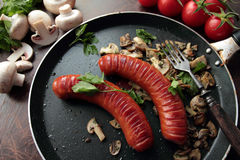 Sausages grilled on a pan with mushrooms Stock Photography